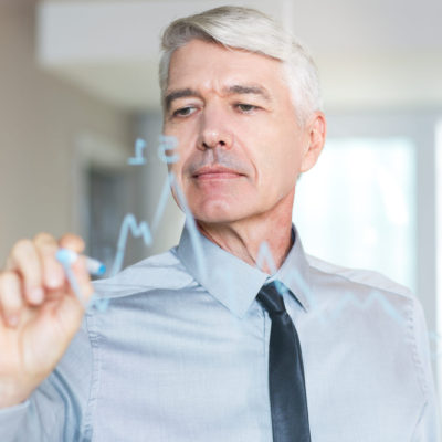 Serious senior Caucasian businessman wearing shirt and tie, drawing line graph on glass board with tip marker