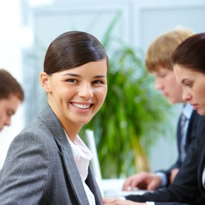 Portrait of smiling woman looking at camera on the background of working colleagues